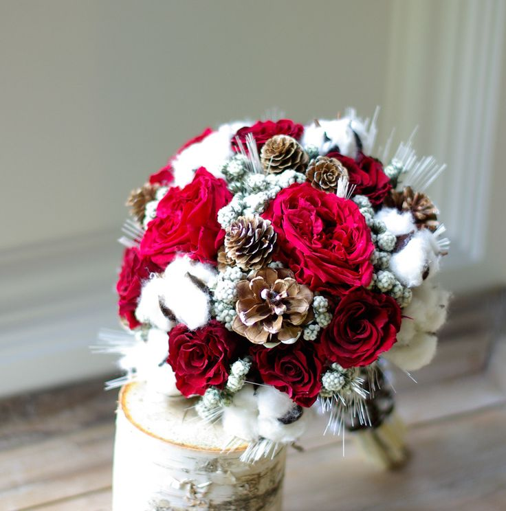 Wed in Winter Made with all Preserved flowers and natural materials. Gorgeous winter bridal bouquet with preserved red garden roses and red standard roses, cotton bolls, pine cones, and white wheat with cozy brown fabric stem wrap and pearl vine over-wrap. This is perfect for the winter bride wanting flowers that wont be problematic in cold temperatures. This bouquet is made with all real flowers preserved to last long past the wedding day.