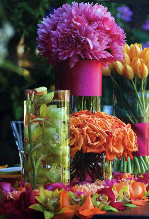 Vibrant bouquets in clear vases wrapped in bright ribbon