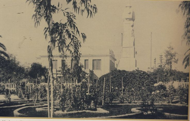 Η πλατεία Ελευθερίας με τον κήπο της και το άγαλμα του Άγνωστου Στρατιώτη και πίσω ακριβώς το κτίριο της Νομαρχίας. Καρτ-ποστάλ Αλικιώτη, δεκαετία 1940-1950