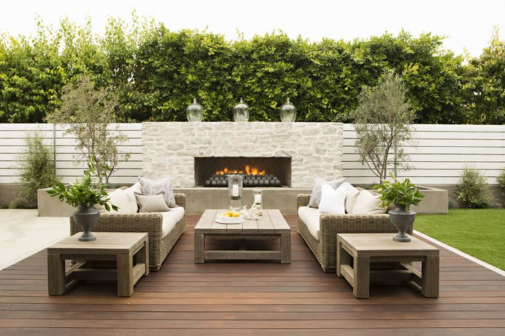 vertical white fence. outdoor fireplace in the wall. clean and modern outdoor space.