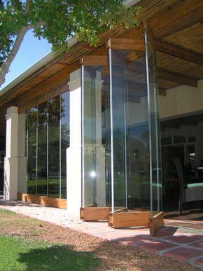 Grandi vetrate pieghevoli senza cornice, pannelli in legno nella parte inferiore e superiore.
