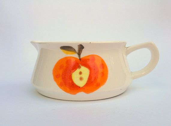 Mid century little ceramic gravy boat. Off white glazed ceramic with a bright orange hand-painted apple. A brown hand painted stripe on the handle. Looks very Scandinavian in design. Excellent .condition Dimensions: 17 cm wide x 6 cm tall
