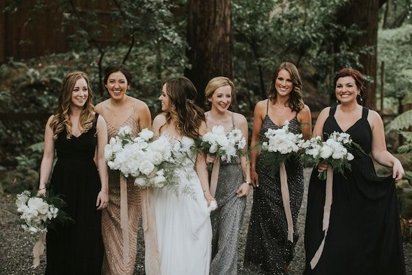 Gone are the days when bridesmaid dresses have to match one another. Choose dresses that have a similar pattern or color family. A jungle wedding could have a color palette or pattern that is seen in the whole bridal party. | Gray, tan and black mismatched bridesmaid dresses with beading