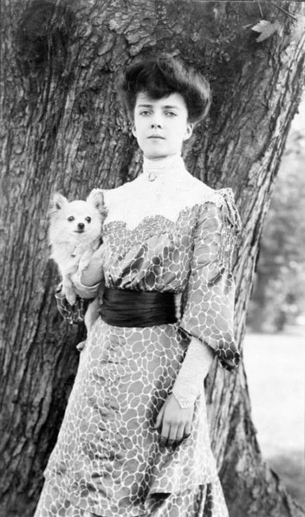 "Alice Roosevelt with her dog Leo. She smoked cigarettes in public, chewed gum, placed bets with bookies, rode in cars with men, stayed out late partying, and kept a pet snake named Emily Spinach, which she often wore wrapped around one arm and took to parties.  Her father President Theodore Roosevelt once said of her ""I can either run the country or I can attend to Alice, but I cannot possibly do both."" 1902"