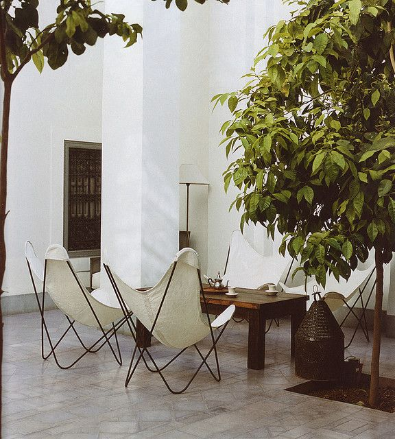 Outdoor living room, white lounge chairs, wooden table, trees, white walls