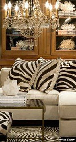 Gorgeous white sectional sofa with zebra pillows. Love the chandelier along with coral and crystal display specimens.