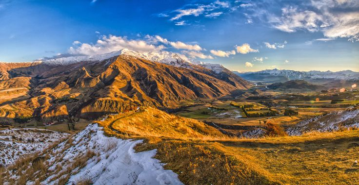 Afternoon glow over Arrowtown, The Remarkables and Queenstown in the distance