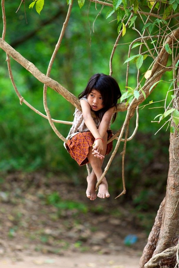 """Photo and caption by Stephen Bures: """"A Khmer Child plays in the jungle trees at…"""