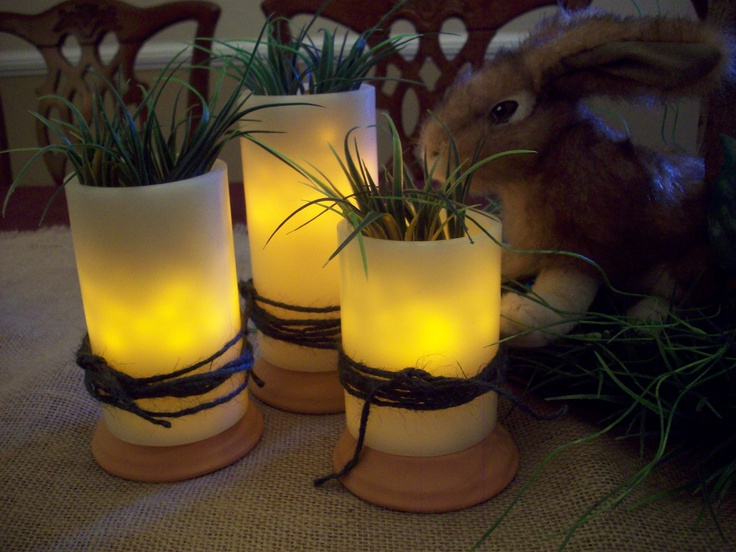 Electric pillar candle luminaires, I added glass beads; topped with plastic grass; tied with jute; placed on inverted clay saucers.