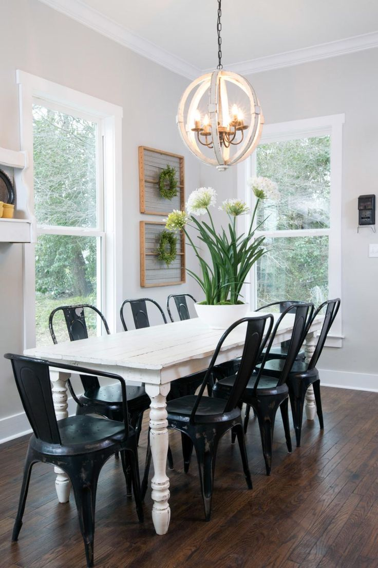 A white farm table and dark metal chairs provides a sleek look and sharp contrast in the dining room. Joanna scoured her warehouse for just the right chandelier for the neo-rustic setting.