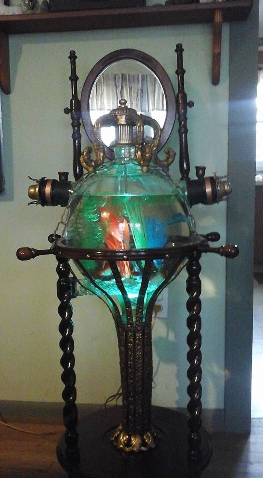 Victorian Steampunk fish tank. This is made with all antique parts. The big glass bowl is from a milker machine and the base used to hold basin and bowl for washing. Extra parts are from a old chandelier. Wish you could see it live in person as photos do no justice to this. At night it creates all kinds of colors on the ceiling because it is has a remote control LED light that changes colors.
