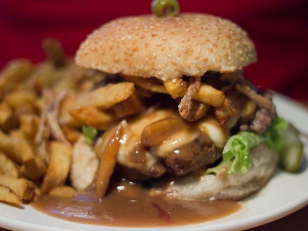poutine burger from the pink bicycle in victoria, bc: burger topped with fries, rosemary gravy and cheese curds