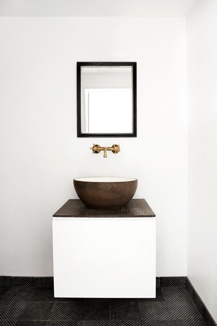 Clean and crisp bathroom vanity, sink, faucet, mirror. Nice combination of materials. Black floor.
