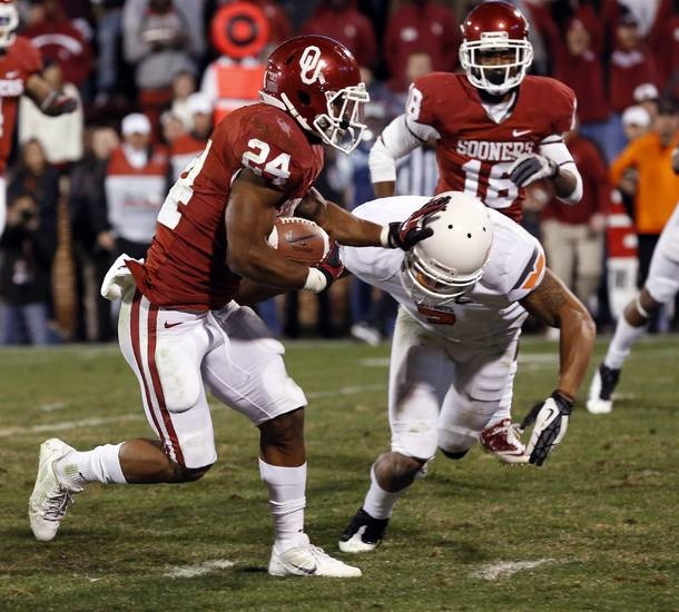 Oklahoma's Brennan Clay (24) pushes aside Oklahoma State's Shamiel Gary (7) and scores the game winning touchdown of the Bedlam college football game in which  the University of Oklahoma Sooners (OU) defeated the Oklahoma State University Cowboys (OSU) 51-48 in overtime at Gaylord Family-Oklahoma Memorial Stadium in Norman, Okla., Saturday, Nov. 24, 2012. Photo by Steve Sisney, The Oklahoman