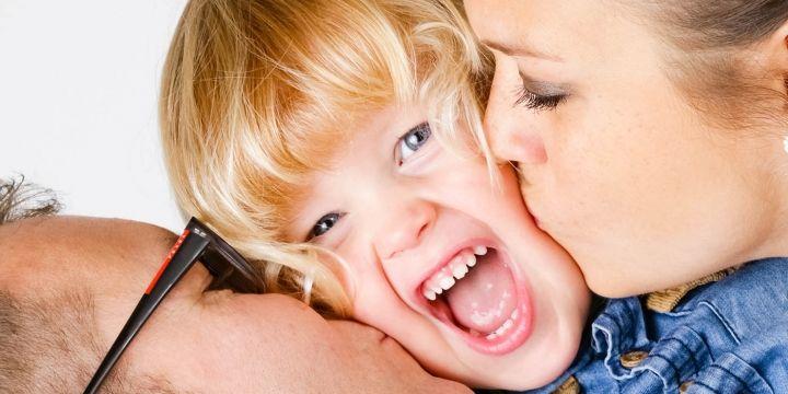 Mooie foto met vader moeder die kindje kussen