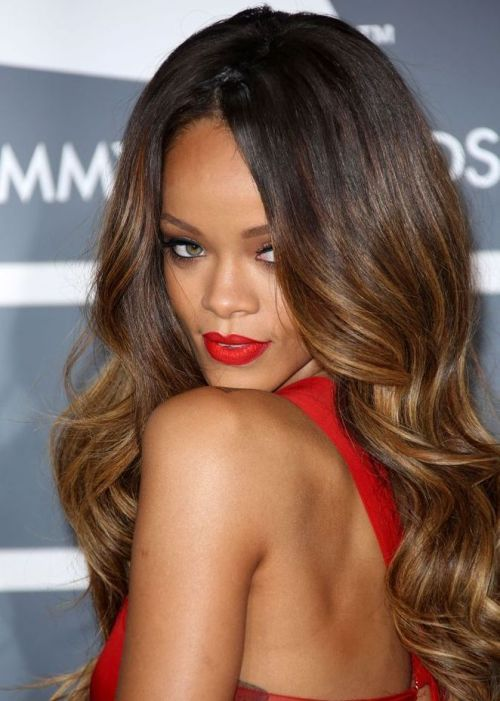 Songstress Rihanna rocks a golden brown ombre fade that gives her long, structured curls a dramatic finish. Ask your stylist to add caramel undertones and golden highlights for extra depth and vibrant color.