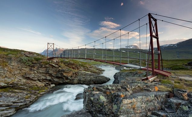 A suspension bridge spans a river in the Tjaekta Valley, which is part of Sweden's Kungsleden, or King´s Trail. The trail covers one of Europe's last swaths of genuinely pristine wilderness, 100 miles north of the Arctic Circle.
