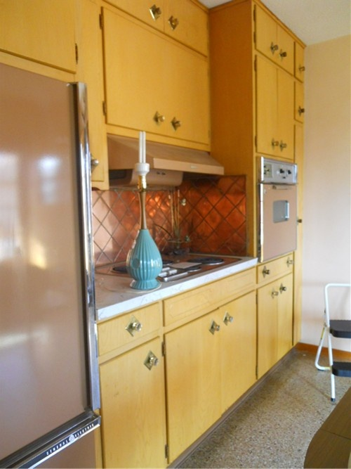 mid century kitchen. Copper tiles back splash.