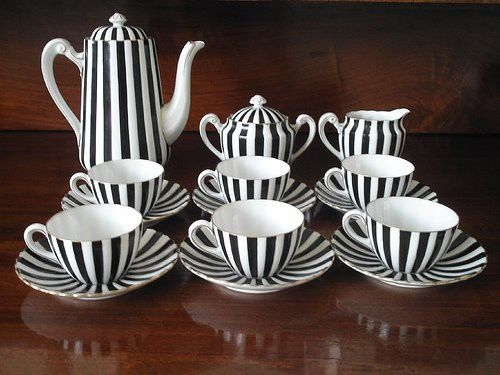 black and white tea set with teapot, creamer, suger and cups.