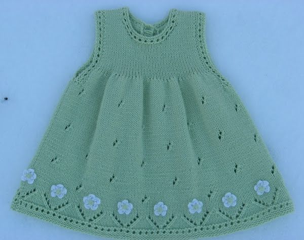 Vestido para niña, tejido con dos agujas, calado, con aplicaciones de flores tejidas a crochet, en el ruedo. [