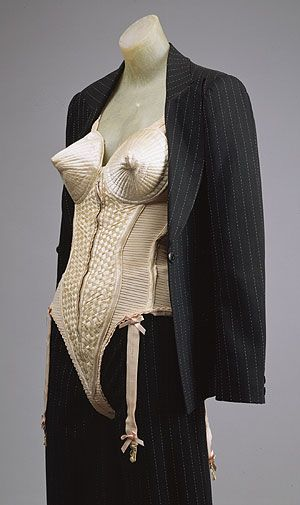 "Suit and Bustier, 1990  Designed by Jean-Paul Gaultier for Madonna in the 1990 ""Blond Ambition"" World Tour                                                                                                 Broken pinstripe slashed jacket and trousers, peach silk/Lycra corset     Loan, Madonna Ciccone                                                                                                                         Metropolitan Museum of Art Costume Institute"