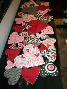 DIY Valentine's Day table runner - Cut out a bunch of hearts for the kids and let them paste all the hearts over a black sheet of paper.