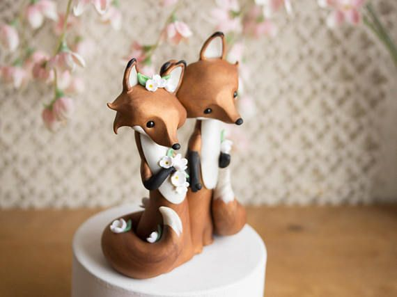 This keepsake wedding cake topper features a pair of Red Foxes dressed for their wedding. The bride is adorned with white flowers and the groom sports a boutonniere and a black bow tie. They are holding hands and their tails curve around them towards the front. I sculpted them by hand with a custom-blended polymer compound that has a subtle sparkle and marbling. Their eyes are Swarovski crystal pearls and they stand just under 5-inches tall.  You will receive the exact same sculpture as seen…