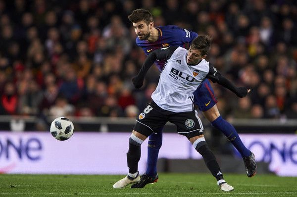 Gerard Pique of FC Barcelona competes for the ball with Luciano Vietto of Valencia CF during the Copa de Rey semi-final second leg match between Valencia and Barcelona on February 8, 2018 in Valencia, Spain.