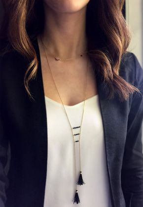 Long tassel necklace.  This necklace features two hand-tied silk tassels hanging from a delicate gold chain. Three lines of tiny onyx beads attach the