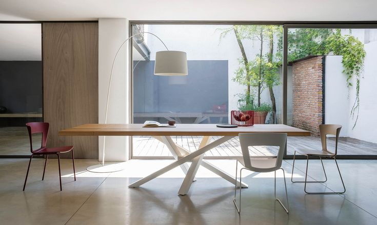 The Shangai solid wood extendable dining table features a solid oak top and an asymmetrical cross leg base.