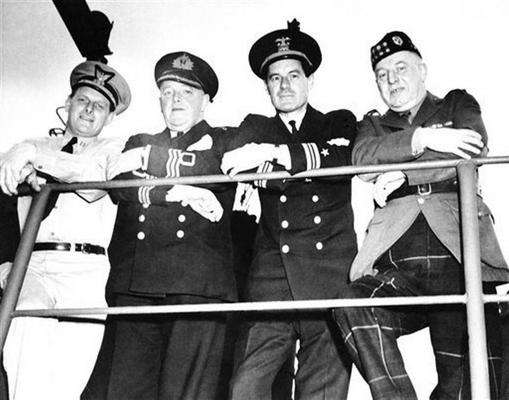United in the common objective of victory for Allied Arms, the officers of Four Services Line the rail on the bridge of a coast guard-manned LST (Landing Ship, Tanks) at a British Port on June 7, 1944. Left to right: Coast Guard Lt. John A. Salt, Miami, Fla., Commander of the LST; Commander Campbell Ross, RNVR, London, England; Lt. Comm. E. G. Janeway, USN, Oyster Bay, Long Island, N.Y.; and Lt. Col. E. P. Combe, of Edinburgh, Scotland. (AP Photo) ( England )