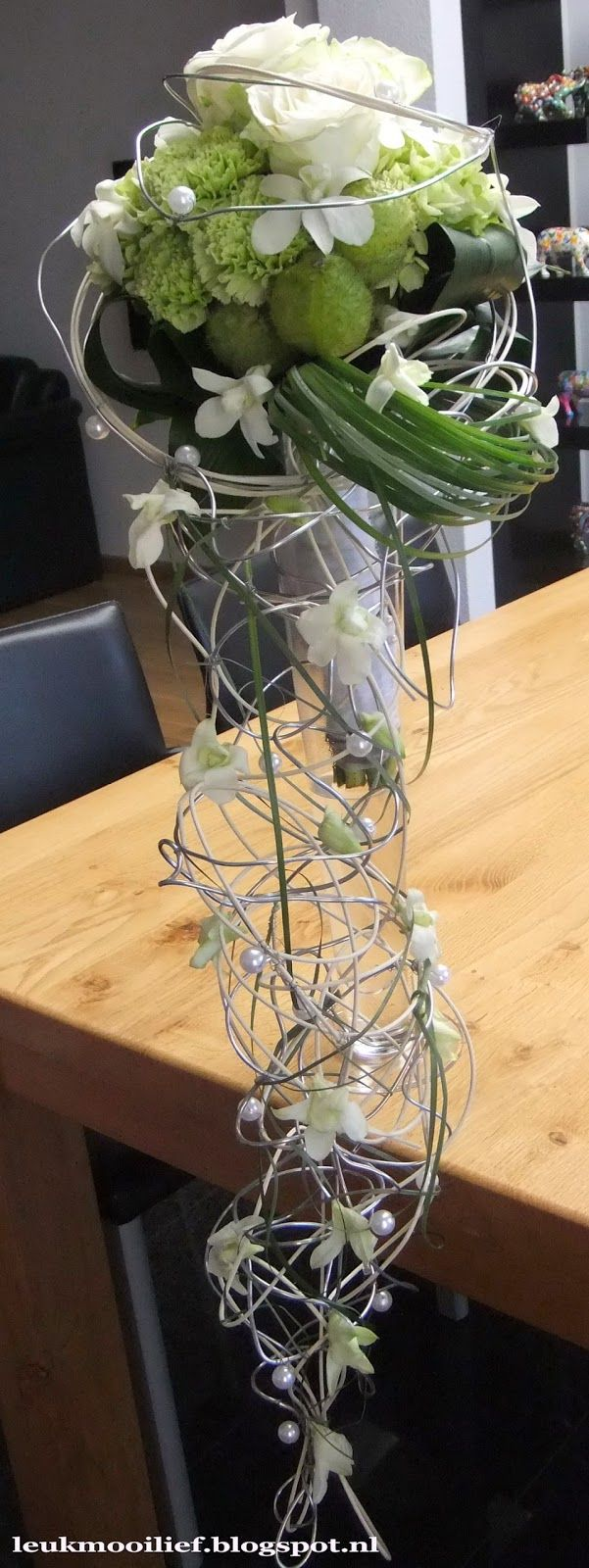 My bridal bouquet - The base is a hand tied bouquet of green Hydrangea, green carnations, large white ' Avelanche ' Roses, Asclepia ' Moby Dicks ', Dendrobium nobile and Aspidistra leaves, with a hanging point of wire frame with white Wicker, bear grass and pearls. The orchids are processed with glue technique. The stems are finished with a remnant of the wedding dress and pearls. | Leuk Mooi Lief