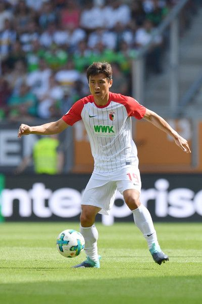 Ja Cheol Koo Photos - Ja-Cheol Koo  of FC Augsburg plays the ball during the Bundesliga match between FC Augsburg and Borussia Moenchengladbach at WWK-Arena on August 26, 2017 in Augsburg, Germany. - FC Augsburg v Borussia Moenchengladbach - Bundesliga