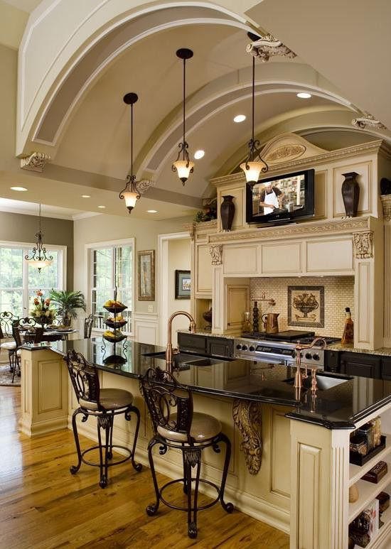 Cream colored kitchen with the black granite, so classic.  And I absolutely love the copper.  That TV looks a bit high for viewing though, but maybe not.