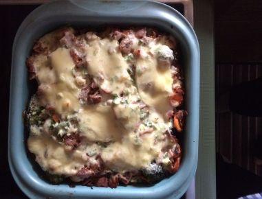 Für den Brokkoli-Karottenauflauf Zwiebel würfeln, Karotten in Scheiben schneiden und beides in etwas Öl anbraten, salzen und pfeffern. Brokkoli in