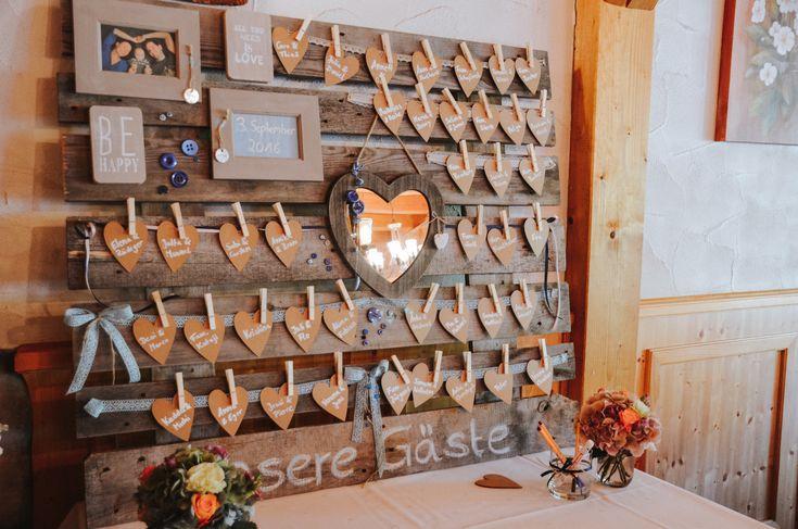 Sitzplan für eine Hochzeit auf einer Holzpalette mit Spitze und Herzchen aus Kraftpapier. Befestigt werden Herzen auf denen die Namen der Gäste stehen mit kleinen Wäscheklammern am Spitzenband. www.annatews.de