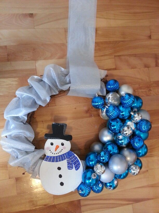 Wreath made with recycled Christmas decorations balls and recycled wreath from Value Village and a wood snowman that I painted from Michaels. The ribbon is from the dollar store