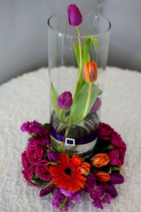 This Is A 14 Cylinder Glass Vase With Orange Tulips Wrapped Around The Vase We Have Purple