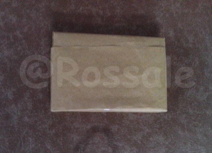 Tampak belakang barang terjual yang siap kirim yang dibungkus oleh kertas cokelat sebagai lapisan kedua