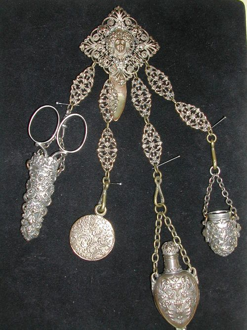 Gilt white metal (silver?). Four attachments for scissors, thimble, pin box and scent. The bottle still has its original glass vial. Dates to the second half of the 19th Century, possibly french.
