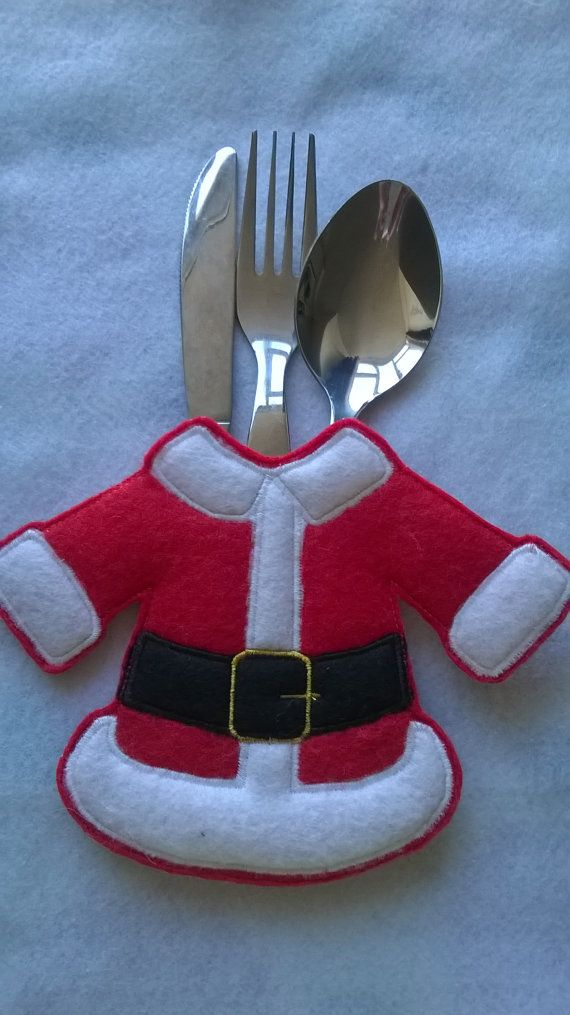 An embroidered Santa felt cutlery holder set for your Christmas table setting. This Christmas Cutlery Holder features Santas coat and trousers and will be a real talking point this holiday season! Practical yet cute!  Embroidered onto soft felt and lined with cream cotton fabric sprinkled with red snowflakes. Or you have the option to order a set which is red cotton fabric and adorned with cream snowflakes. Just let me know when you purchase which lining fabric you would like.  Measures…