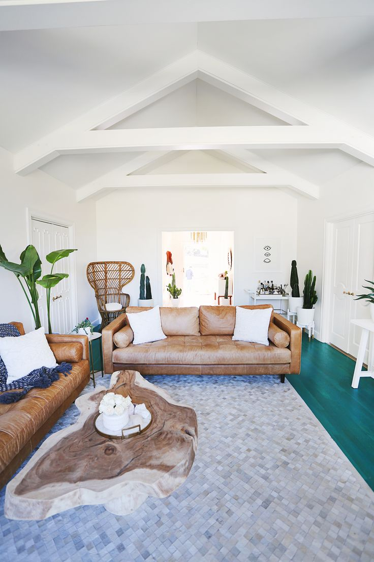 Beautiful living room makeover: white walls and painted beams, teal stained floor, live edge coffee table, tan leather sofas, tons and tons of plants - eclectic with mid-century modern feel
