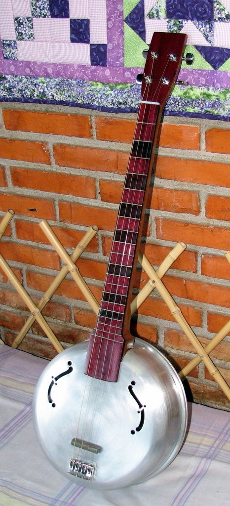 Banjo type guitar I made from an aluminum pot......I live in Costa Rica and am very limited on tools and supplies.......I only used hand tools (hand saw, coping saw, files, etc.) and an cordless drill........The neck is made from an old piece of almond wood.......Very straight grained and very hard.......I overlayed the headstock with purple heart wood (donated by a Costa Rican friend) and also made the fret board from purple heart.......The nut and bridge are made from the old handles....