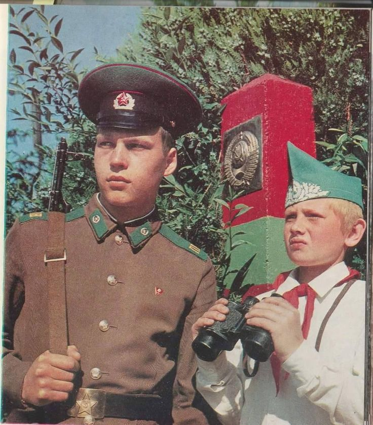 A Soviet border guard observing the border with a young pioneer.