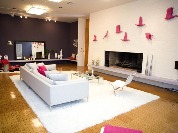 Antonio and his teammates Lonni and Amy set the scene for this glamorous living room with bright white walls and furniture. To add color to the space, they paint an accent wall purplish-gray and add pops of hot pink.
