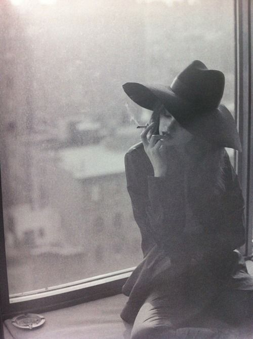 window portrait in black and white, woman with hat