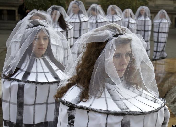 Romanian students dressed as caged brides attend an event to raise awareness to the risks of human trafficking and sexual exploitation faced by young girls lured by the prospect of a better paying job abroad, in Bucharest, Romania, Saturday, Nov. 19, 2011. (AP)