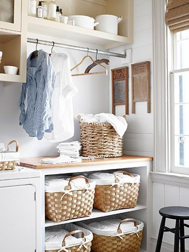 Beautiful Laundry Rooms | Design Tip: Laundry Room Styles This laundry room seamlessly blends white, beige, and sand tones for a simple and refreshing design.  The old washboards and enamel basins are perfect for adding rustic elements to the overall clean look. The over-sized baskets fit beautifully in the cabinet for additional storage.