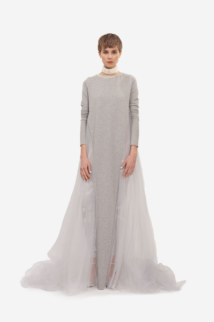 """MAXI DRESS """"WINGS"""" Shorthaired model wearing an occasion or wedding dress made of cotton and tulle. The dress has long sleeves and semitransparent back part with trail. Elastic overall with original print underneath."""