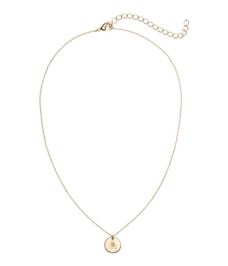 A/Goldfarben. Feine Halskette aus Metall. Die Kette hat einen runden, flachen Anhänger mit ausgestanztem Buchstaben. Verstellbare Länge, 40-48 cm.
